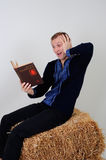 Man in the Ukrainian national costume with a book about busine. The man in the Ukrainian national dress and jeans sitting on a haystack with a book of business Stock Image