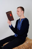 Man in the Ukrainian national costume with a book Capital in R. The man in the Ukrainian national dress and jeans sitting on a haystack with a book capital in Stock Photos