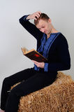 A man in the Ukrainian national costume from the economic book i. The man in the Ukrainian national dress and jeans sitting on a haystack with economic book in Stock Photography