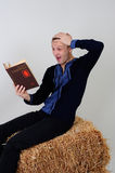 A man in the Ukrainian national costume from the economic book i. The man in the Ukrainian national dress and jeans sitting on a haystack with economic book in Stock Image