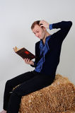 Man in the Ukrainian national costume from the economic book i. The man in the Ukrainian national dress and jeans sitting on a haystack with economic book in Stock Images