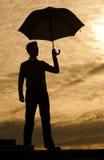 Man with umbrella. Business man holding umbrella against sunset Stock Photo