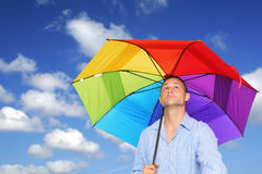 Man and Umbrella. Man in shirt under bright umbrella with blue sky and clouds background Stock Photography