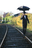 Man with umbrella. Man dressed with black suit with umbrella walking on railway track Stock Photography
