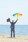 Man with umbrella on beach Stock Photos