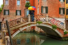 Man with umbrella on bridge over Venetian canal Stock Photos