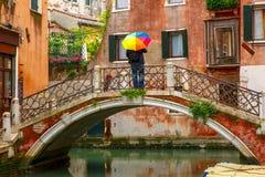 Man with umbrella on bridge over Venetian canal Stock Photo