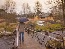 A man with an umbrella goes to church on a bridge. In Sankt Petersburg Stock Images