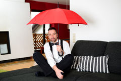 Man with umbrella in the living room. Man in white shirt with bow-tie sitting in the living room with umbrella Royalty Free Stock Photos