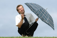 Man with umbrella looking into skies Stock Photo