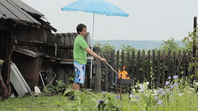 Man with umbrella near the fire for barbecue. The rain is falling, an old building with a fence in the background stock footage