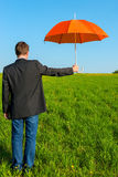 Man with an umbrella ready to shelter Stock Images