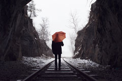 Man with umbrella standing on old railroad tracks vanishing Stock Photography