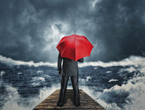 Man with umbrella standing on the pier. Man with red umbrella standing back on the pier at night storm Royalty Free Stock Image
