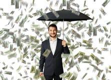 Man with umbrella standing under money rain Stock Image
