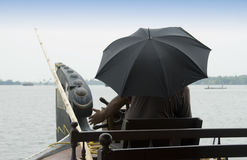 Man with umbrella steers a Houseboat Royalty Free Stock Images