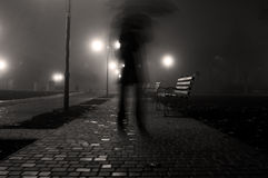 Man with umbrella walking in the in the night park Stock Images