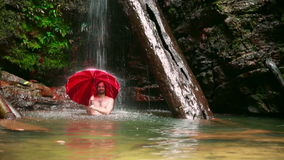Man with umbrella at waterfall in borneo rainforest stock footage