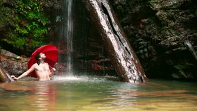 Man with umbrella at waterfall in borneo rainforest stock video footage