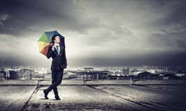 Man with umbrella. Young handsome businessman in suit with colorful umbrella royalty free stock images