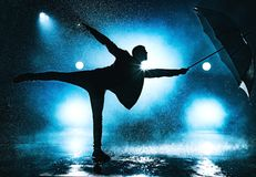 Man with umbrella. Young strange man dancing with umbrella under the rain. Dramatic blue colors stock photos