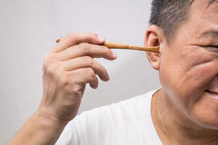 Man un-hygienically cleaning ear using wooden stick Stock Images