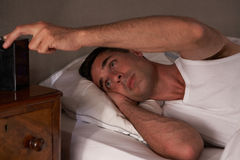 Man unable to sleep. Looking at clock Stock Image