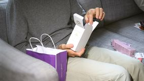 Man unboxing on the couch cosmetics containing L`Artisan Parfume Royalty Free Stock Image
