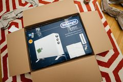 Man unboxing heating convecter DeLonghi from Amazon. PARIS, FRANCE - FEB 7, 2018: Unboxing large cardboard box containing italian DeLonghi air convection heater royalty free stock photos