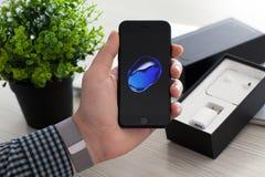 Man unboxing iPhone 7 Jet Black Onyx over MacBook Pro royalty free stock image