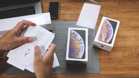 Man unboxing iPhone Xs Max Xr reading manual and admiring stickers. PARIS, FRANCE - SEPTEMBER 21, 2018: Apple fan boy unboxing latest new Apple iPhone Xs Max and stock video footage
