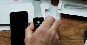 Man unboxing new Apple Watch wearable smartwatch computer. Paris, France - circa 2018: POV man unboxing unpacking latest Apple Watch Series 3 GPS LTE smartwatch stock video footage