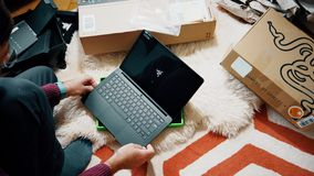 Man unboxing new gamer Razer Blade Stealth laptop sent by Amazon customize settings. PARIS, FRANCE - CIRCA 2017: Man unboxing new gamer professional aluminum stock footage