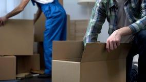 Man unboxing saker i den nya lägenheten, arbetaren för det rörande företaget som kommer med askar royaltyfri fotografi