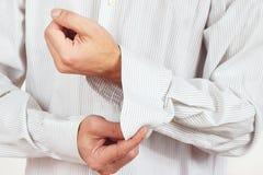 Man unbuttons his sleeve bright shirt closeup Stock Image
