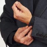Man unbuttons his sleeve business suit closeup Stock Images