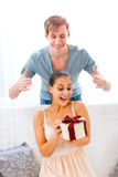 Man uncover eyes of girlfriend with present. Young men uncover eyes of surprised girlfriend with present in hand Stock Photos