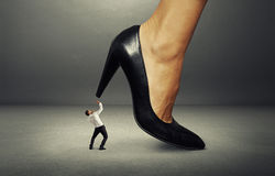 Man under big female heel Royalty Free Stock Image