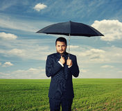 Man under black umbrella at outdoor Stock Image