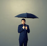 Man under black umbrella over dark Stock Photography
