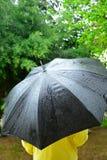 Man under the  black umbrella while rainig Stock Photo