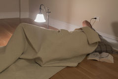 Man under blanket on floor Royalty Free Stock Photography