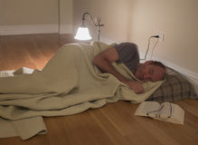 Man under blanket on floor Royalty Free Stock Images
