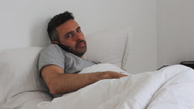 Man under the blanket with smartphone and tablet Stock Image