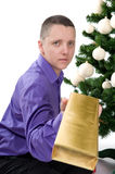 Man under christmas tree is giving a gift Stock Photo