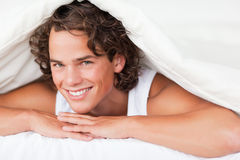 Man under a duvet with a knowing smile Stock Images