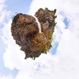 Man under en bergvattenfall i form av en sten av heaen royaltyfria bilder