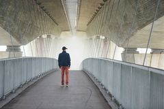 Man under highway brige in mysterious morning fog. Man on the footbridge under highway bridge in mysterious morning fog. Prague, Czech Republic Royalty Free Stock Photo