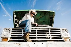 Man under the hood of his truck. Man in cowboy hat under the hood of truck Stock Image