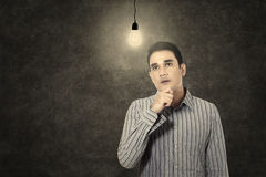 Man under lit bulb thinking of idea. Young man under lit bulb thinking of idea in a classroom Stock Image